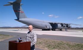 U.S. Air Force Brig. Gen. Steven Vautrain addresses reporters at  Westover Air Force Reserve Base with a C-5 as backdrop. The base will loose half the 16 plane fleet of C-5s and 334 jobs will be cut.