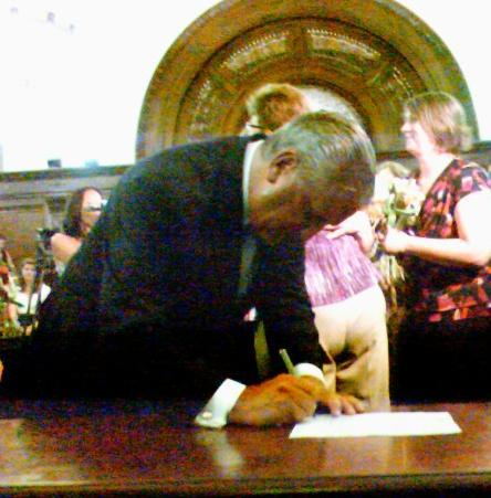 Albany Mayor Jerry Jennings signs documents for a same-sex couple during midnight hour marriages at City Hall.