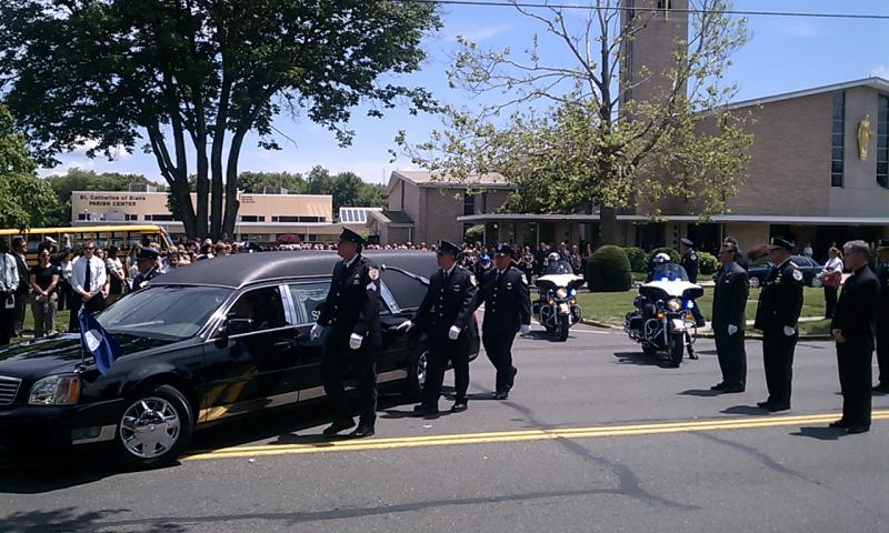 A hearse with the body of Springfield Police Officer Kevin Ambrose leaves the church following his funeral mass