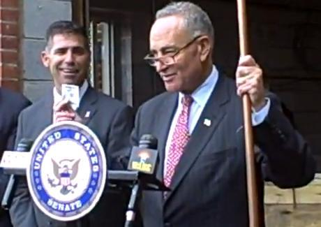 Ulster County Executive Mike Hein looks on as Senator Chuck Schumer uses a $100 bill and a piece of metal as props as he announces a federal initiative to deter metal thefts. (Kingston, NY 10.3.12)