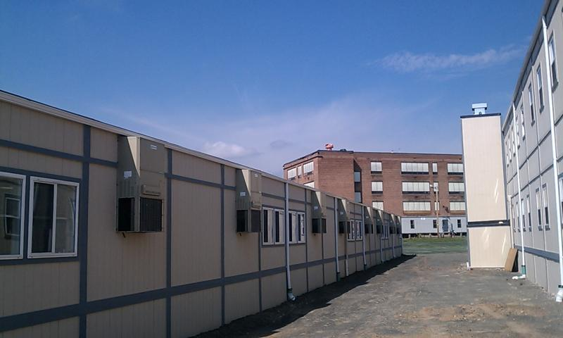 Modular classrooms located on what was the playground of the tornado damaged Elias Brookings school. The damaged school is in the background