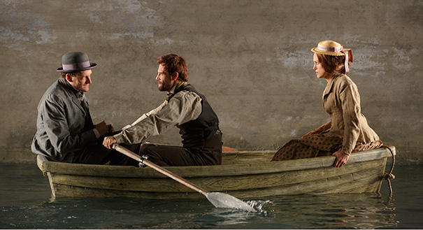 Actors Gabriel Ebert, Matt Ryan, and Keira Knightley on stage in a small rowboat. The boat is in a pool of water upstage which makes it look like they are in a boat on a river.