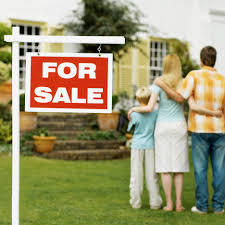 This is a picture of a family in front of a house for sale