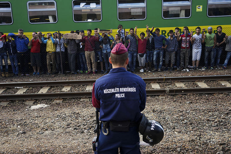 Photo of Syrian refugees at a Budapest railway station with police officer in foreground from September 2015.