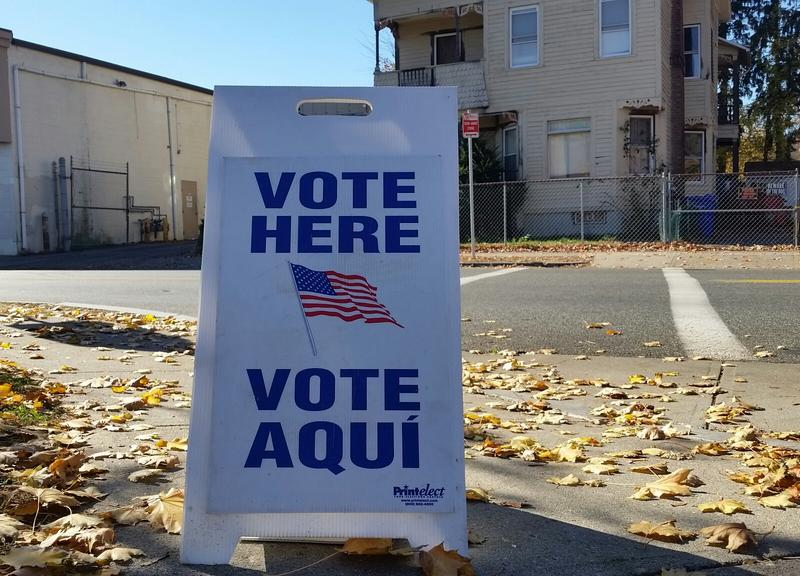 A vote here sign in English and Spanish on sidewalk