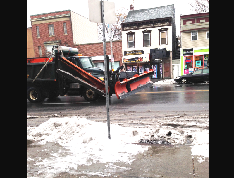 A snow plow cruises past the WAMC studios along Central Avenue in Albany.