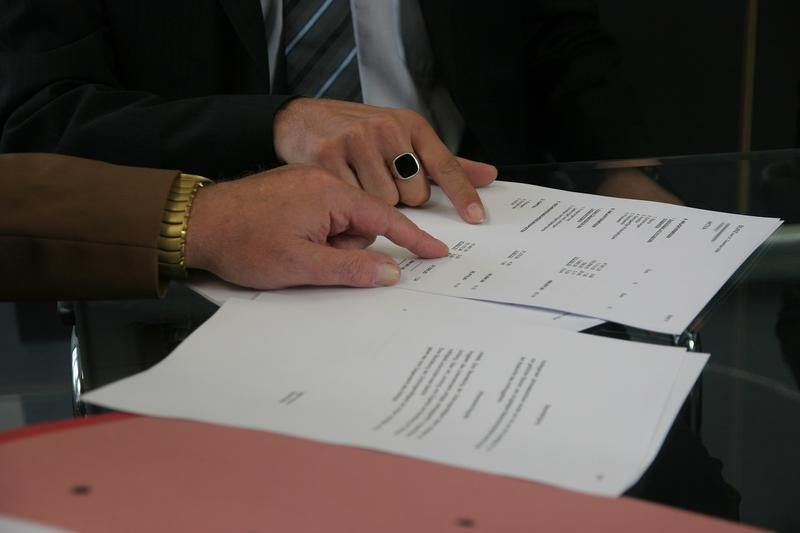 Photo of people's hands reviewing contract
