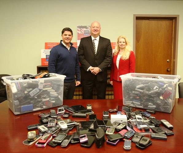 Senator George Amedore with AT&T personnel and some of the mobile phones recently collected.