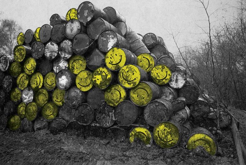 Large pile of hazardous waste barrels - some with smiley faces on the round end