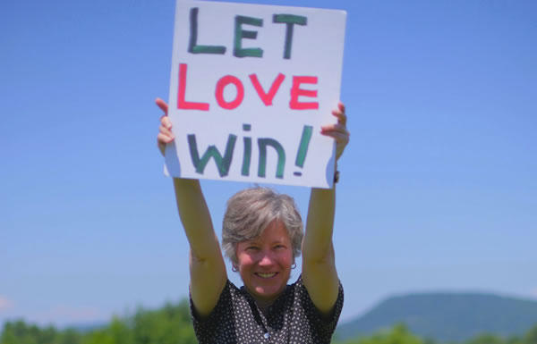 "Woman holding up a sign that says ""LET LOVE WIN!"""