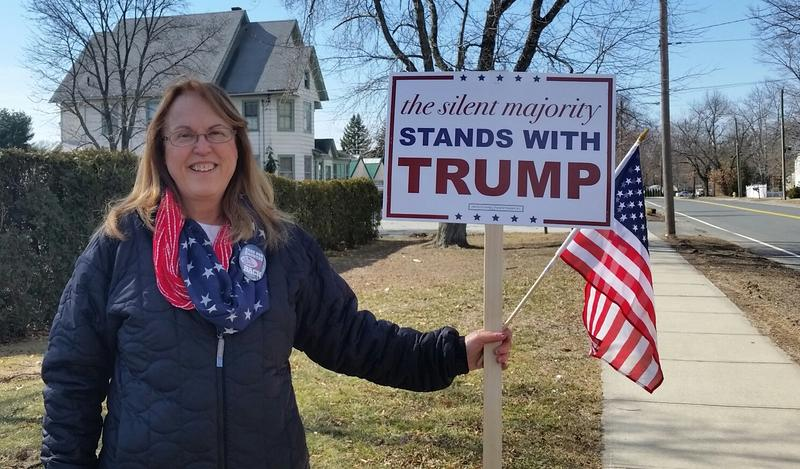woman holds Donald Trump sign and small American flag