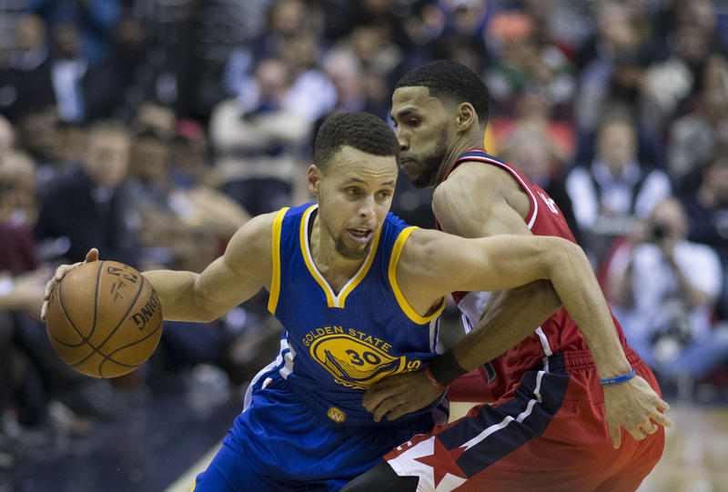 Golden State Warriors' Stephen Curry juking player from Washington.