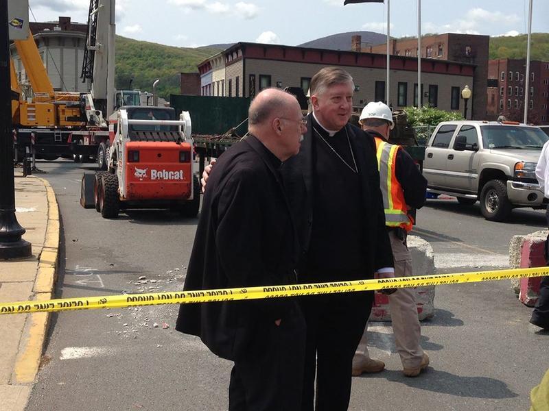 Bishop Rozanski and Rev. William Cyr tour the demolition site.