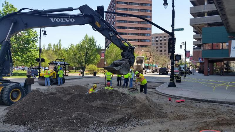 crews work to repair a hole in a street