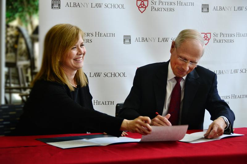 Alicia Ouellette, president and dean of Albany Law School, signs agreement with James K. Reed, M.D., president & CEO of SPHP.