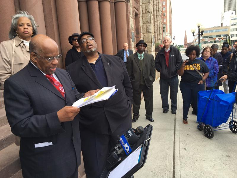 A Black Lives Matter activist records the press conference as Pastor McKinley Johnson addresses the gathering.