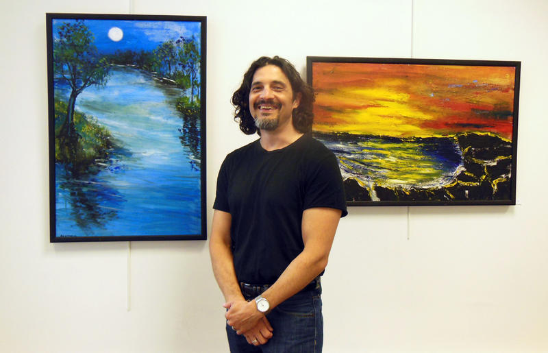 Strand Center Gallery Coordinator David Monette beside Art of the Visually Impaired paintings