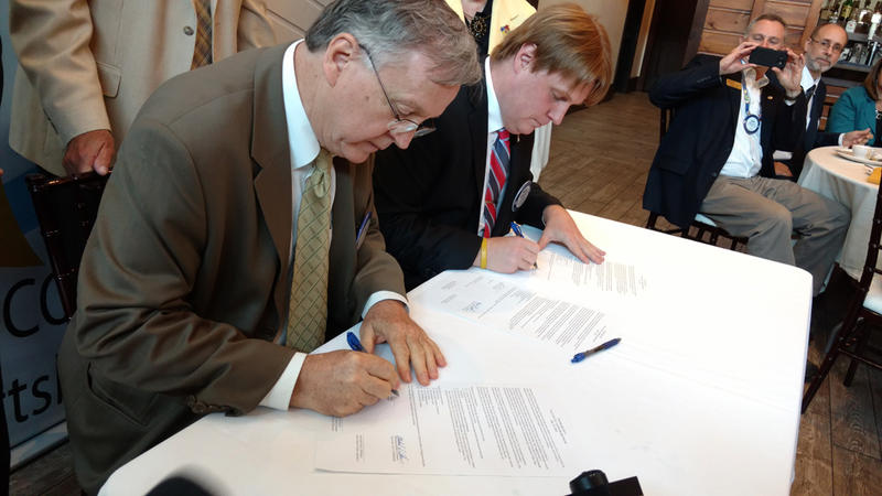 Mayor James Calnon (left) and Supervisor Michael Cashman sign leadership agreement