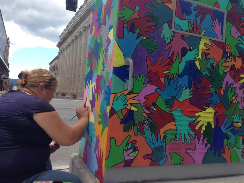 Artist Stacey Healey paints a utility box on North Street in downtown Pittsfield, Massachusetts.