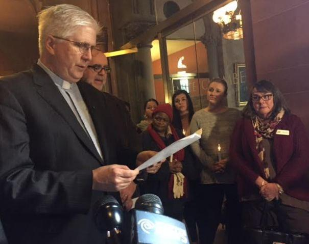 Peter Cook, executive director of the New York State Council of Churches, asks for funding to be freed up, as supporters hold a vigil outside the New York state Senate chamber.
