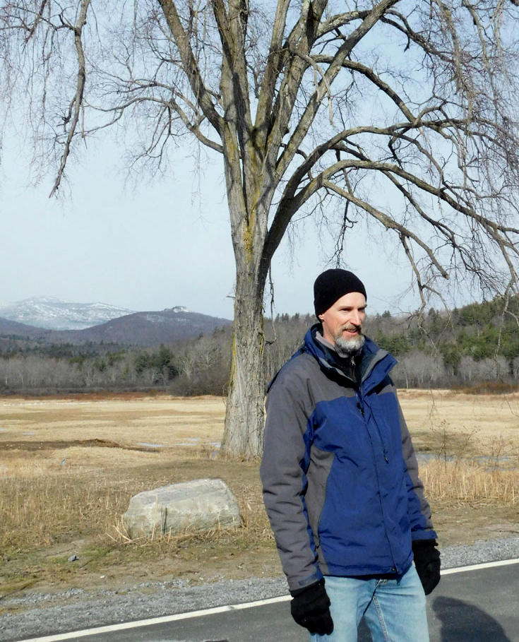 Christian Marks stands in front of elm tree