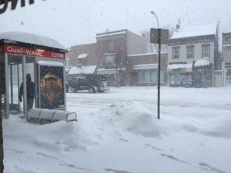 A lone rider waits for a bus as a snow plow passes by along Albany's Central Avenue.
