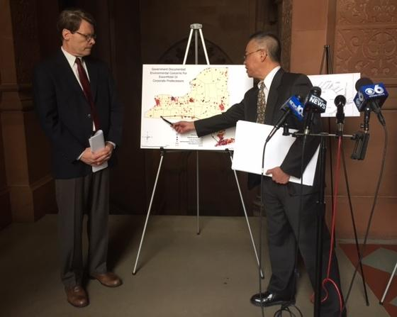NYPIRG's Blair Horner and Toxic Targeting's Walter Hang present documents on unfinished oil spill clean ups in New York.