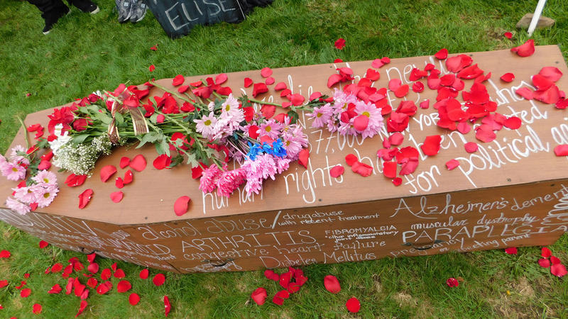 Protest coffin covered in flowers