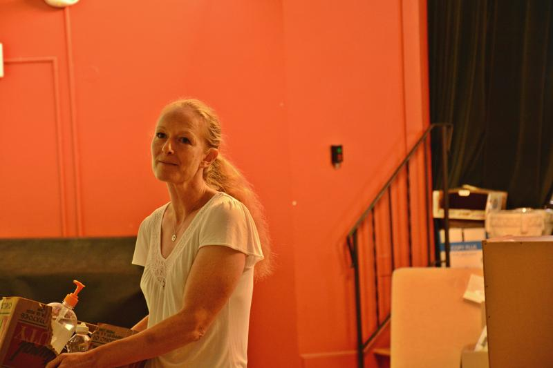 Leaving Director Hilary Greene shifts some boxes around the auditorium getting the spot ready for workshops.