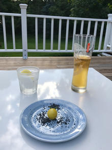 The first homegrown cherry tomato of the season with Hawaiian black lava salt and refreshments