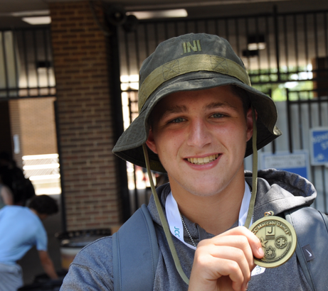 A young man displays a medal he won during Maccabi Games.