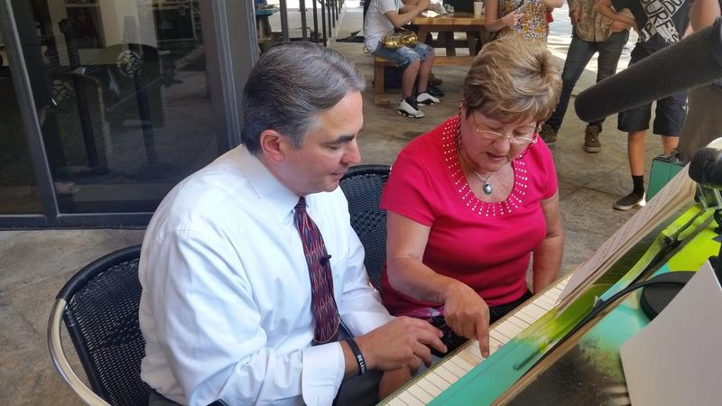 Springfield Mayor Domenic Sarno gets a piano lesson from Sofya Shainskaya at the steet piano outside the office building at 1350 Main Street