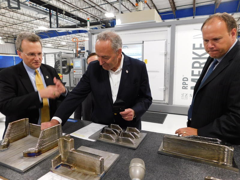 Senator Charles Schumer examines parts manufactured at Norsk Titanium
