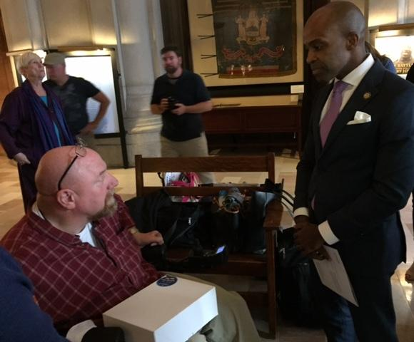 Advocate Gene Hughes gives signed petitions to Governor Cuomo's counsel Alphonso David