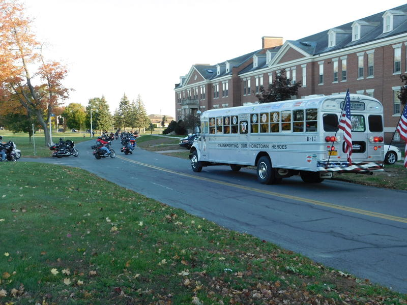 Honor Flight bus is escorted from the ceremony to the airport terminal