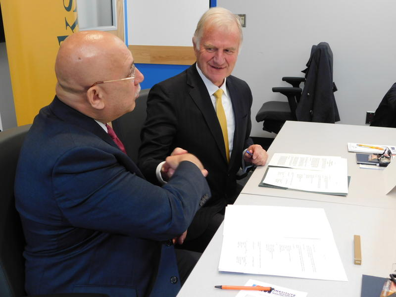 Clinton Community College President Ray DiPasquale (left) and Clarkson University President Tony Collins shake hands after signing the agreement