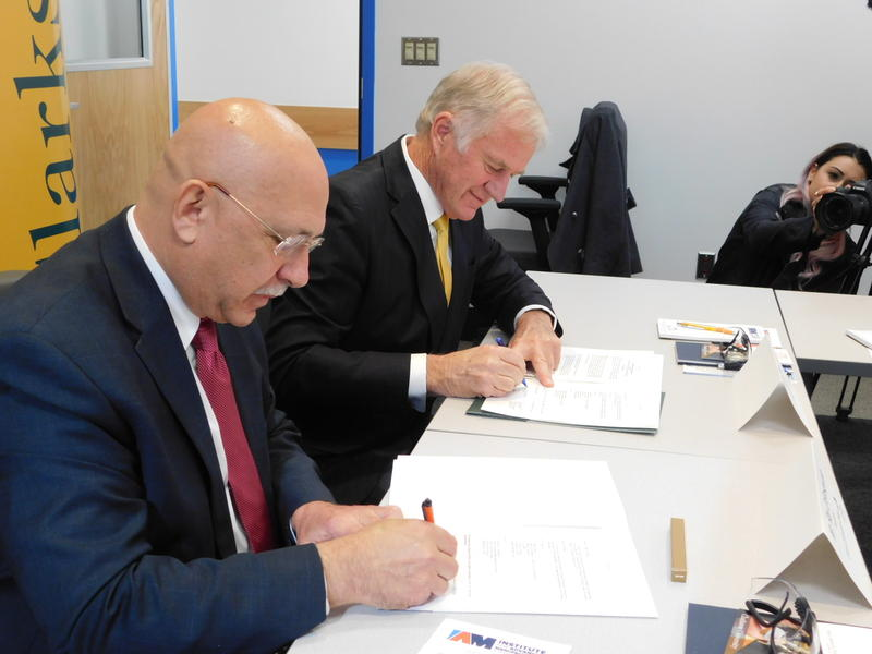 Clinton Community College President Ray DiPasquale (left) and Clarkson University President Tony Collins sign collaborative agreement