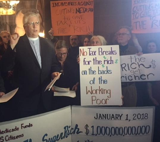 The Reverend Peter Cook, executive director of the New York State council of Churches, speaks against the federal tax overhaul measure at a rally at the State Capitol Friday.