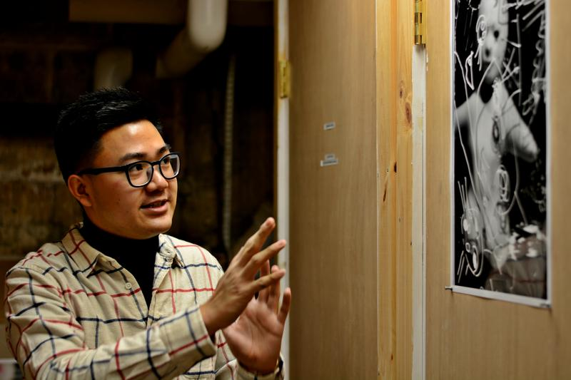 Curator Alex Jen, a Williams College junior, explains the work by Zak Arctander, positioned across from boxes of police evidence.