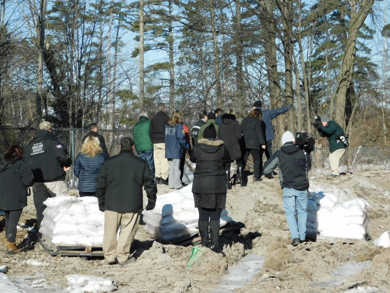 Officials crowd around the governor as he inspects the top of the damaged berm