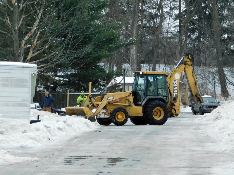 Backhoe clears ice from streets and yards at Underwood Mobile Home Park