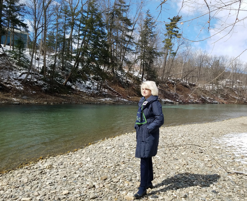 In this photo dated March 2018, Cindy Doran stands near the St. Gobain plant on the river in Hoosick Falls, site of the PFOA contamination.