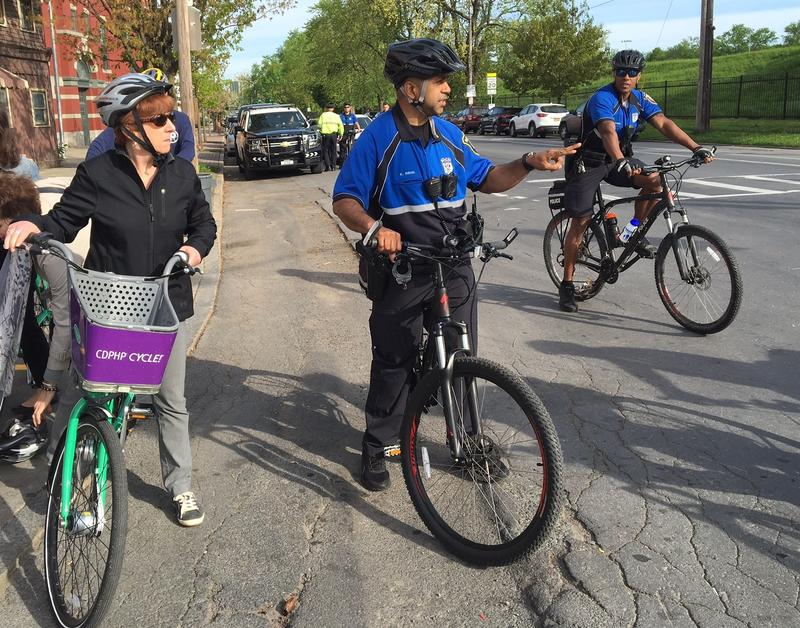 An Albany police officer signals Mayor Kathy Sheehan it's time to ride down Clinton Avenue on Bike To Work Day 2018.