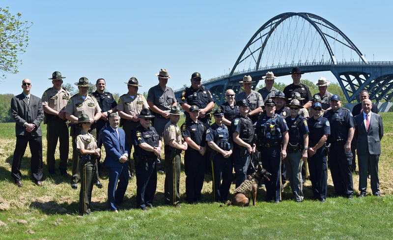 New York and Vermont law enforcement officials pose with the Champlain Bridge in the background