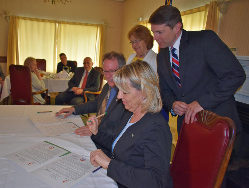 Plattsburgh Mayor Colin Read and Longueuil Mayor Sylvie Parent sign agreement as Assemblyman D. Billy Jones and Senator Betty Little watch