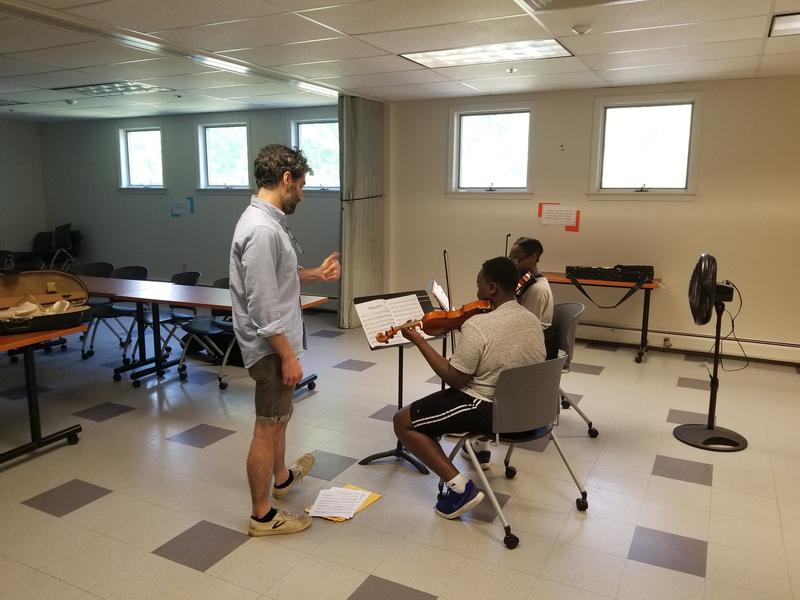 Teaching artist Sean Elligers instructs two students in the Berkshire Children & Families' Kids 4 Harmony program.
