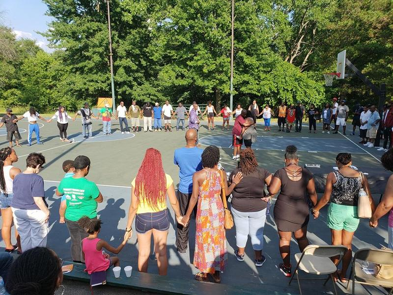Crowd joins hands in prayer circle at Arbor Hill community meeting July 15, 2018.
