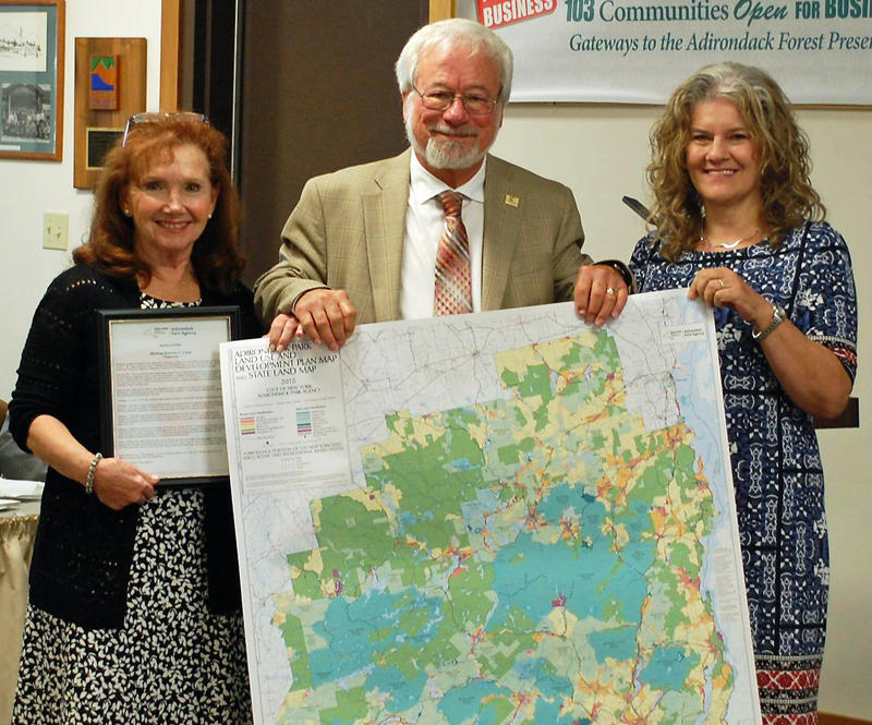 Retiring APA Chairman Sherman Craig (center) is presented with resolution and 2018 Adirondack Park Land Use map from Annette Craig (left) and Executive Director Terry Martino (right)
