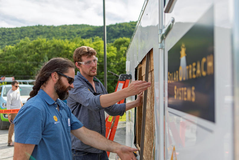 Volunteers from SunCommon build a portable solar-powered trailer