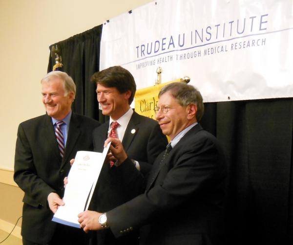 Memorandum of Understanding signed between Clarkson University President Tony Collins (left), Empire State Development President, CEO and Commissioner Kenneth Adams (center), and Trudeau Institute President, Director and CEO Ronald H. Goldfarb (right)